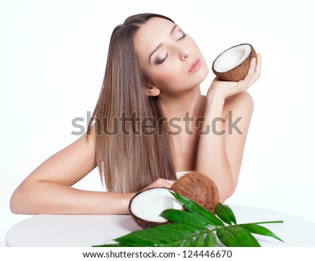 beautiful woman with perfect skin holding coconut over white background - stock photo