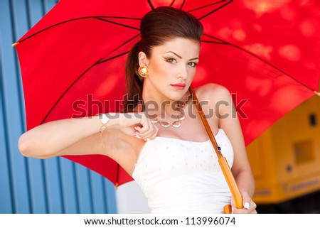 beautiful woman with perfect skin wearing professional make-up holding a red umbrella - stock photo