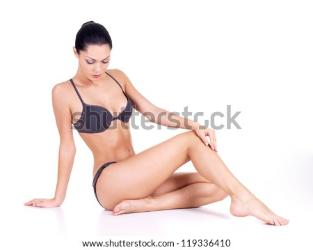 Beautiful woman with perfect slim body sits on white background