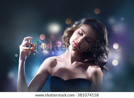 Beautiful woman with perfume bottle on dark background - stock photo