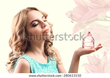 Beautiful woman with perfume bottle on light background - stock photo