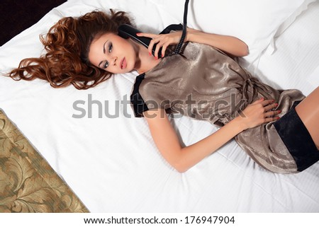 Beautiful woman with phone in the bed - stock photo