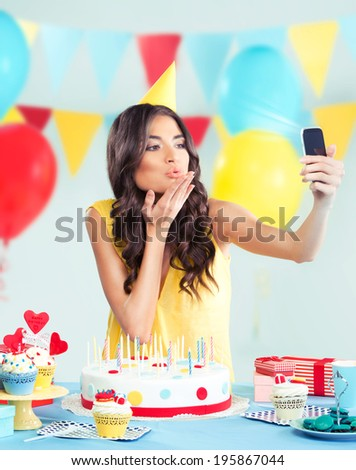 Beautiful woman with phone, sending a kiss - stock photo