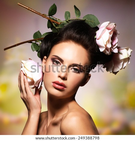 Beautiful  woman with pink flowers in hairs posing over creative color background. Fashion model with creative hairstyle - stock photo