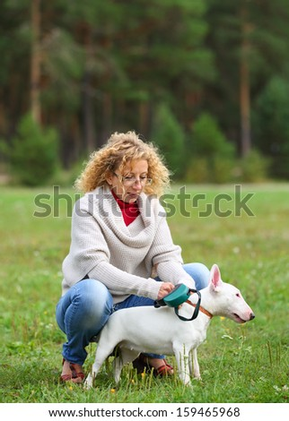 Beautiful woman with playful young dog - stock photo