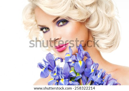 Beautiful woman with purple flowers. Spring Flower.Mother's Day. Springtime. Professional makeup. - stock photo