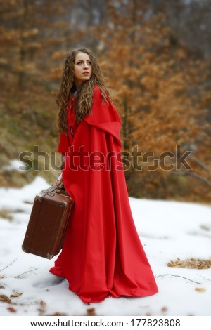 beautiful woman with red cloak and suitcase - stock photo