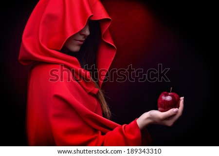 beautiful woman with red cloak holding apple - stock photo