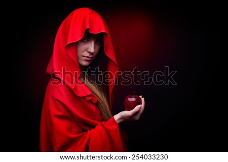 beautiful woman with red cloak holding apple - studio shot - stock photo