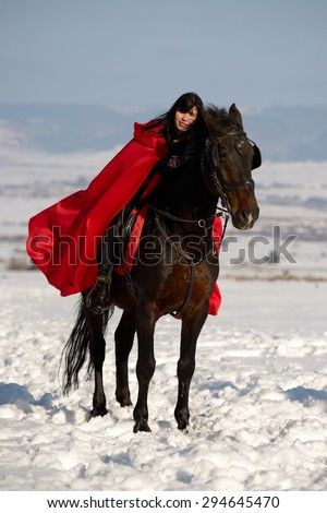 beautiful woman with red cloak with horse outdoor in winter - stock photo