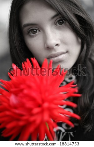 Beautiful woman with red flower. Close-up, shallow DOF, focus on eyes.