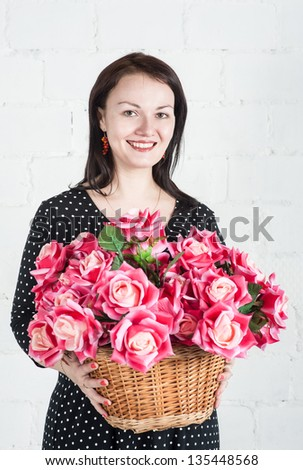 Beautiful woman with red flowers in the basket - stock photo