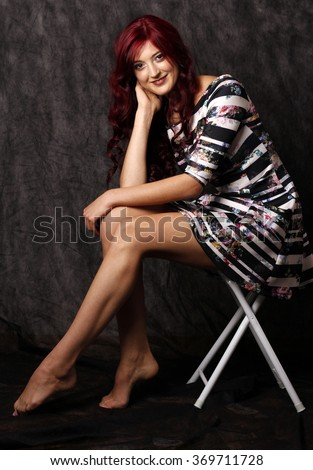 Beautiful woman with red hair and long legs. - stock photo