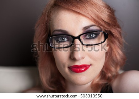 Beautiful Woman with Red hair and wearing black rim glasses