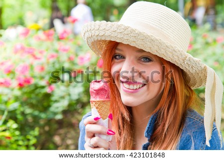 Beautiful woman with red hair  eating a delicious ice cream. Girl relaxing in the park - stock photo