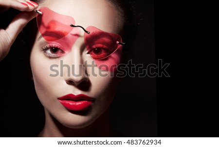 Beautiful woman with red heart shape sunglasses isolated on black background with copyspace.