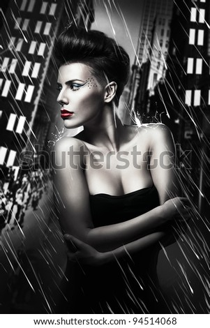 beautiful woman with red lips in rainy city - stock photo