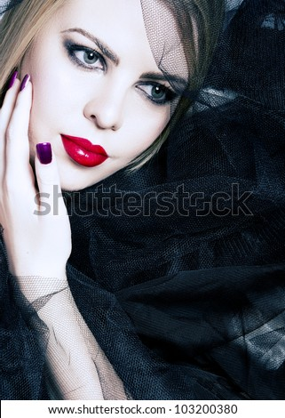beautiful woman with red lips, smoky eyeshadow and purple manicure on the background of black veil with copy space. - stock photo