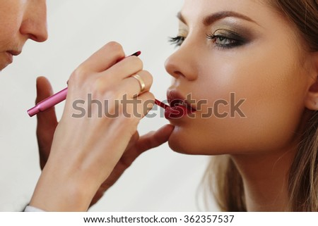 Beautiful woman with red lipstick during make-up