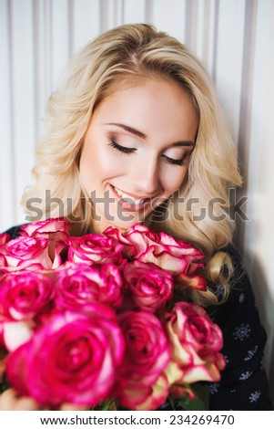 Beautiful woman with red roses bouquet. Valentine gift - stock photo