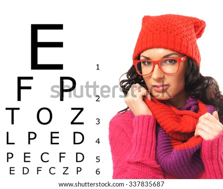 Beautiful woman with red scarf, hat and glasses over test vision table.