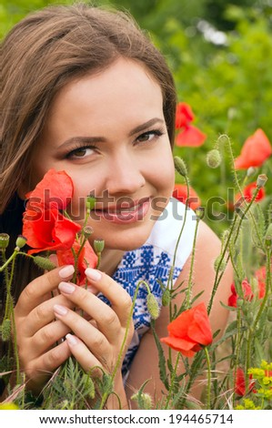 Beautiful woman with red spring flowers in a garden