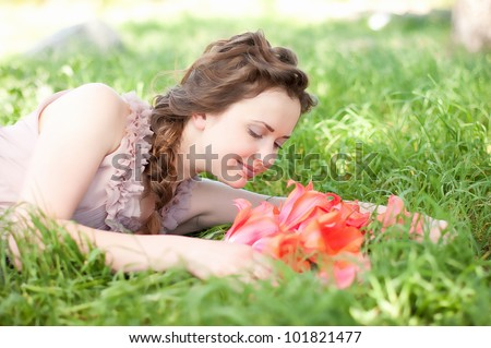 Beautiful woman with red spring tulips in a garden