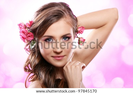 Beautiful woman with roses in hair over pink background - stock photo