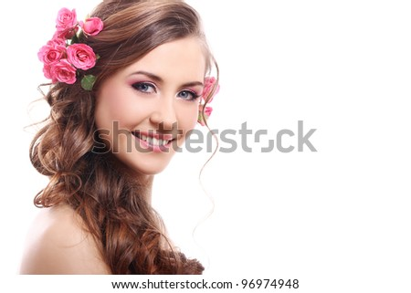 Beautiful woman with roses in hair over white background - stock photo