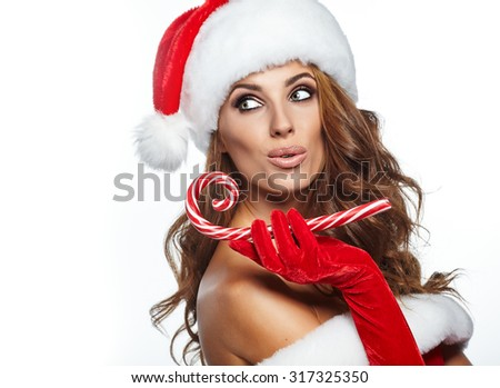 Beautiful woman with santa costume  holding red-white Christmas Lollipop - stock photo