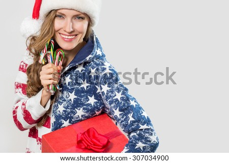 Beautiful woman with santa hat holding christmas candy canes - stock photo