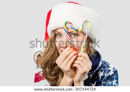 Beautiful woman with santa hat holding christmas candy canes, focus on woman - stock photo