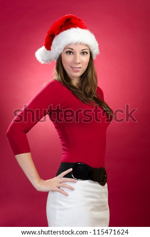 Beautiful woman with santa hat on a red background - stock photo