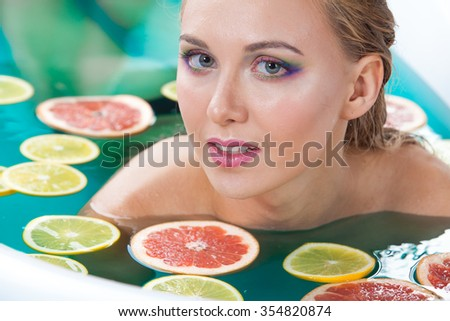 Beautiful woman with shiny skin in water with fruit