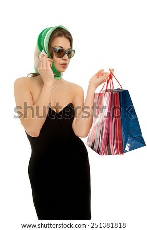 Beautiful woman with shopping bags calling by phone isolated on white - stock photo