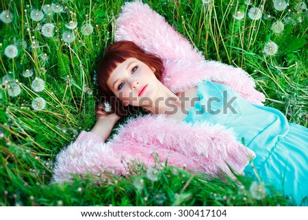 Beautiful woman with short hair in a fluffy pink jacket lying on green grass among the dandelions - stock photo