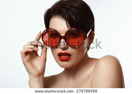 beautiful woman with short hair wearing glasses with red lenses