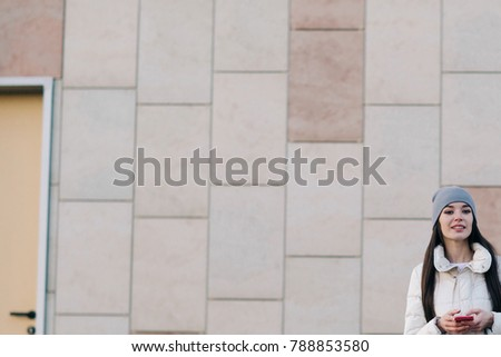 Beautiful Woman with smartphone city near wall in winter coat.