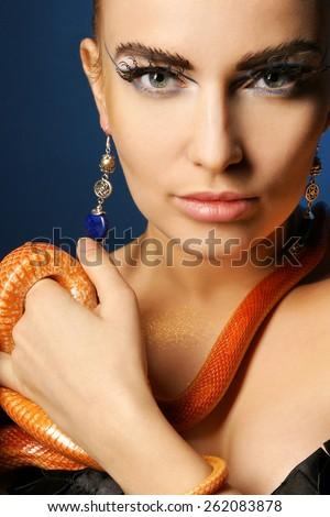 Beautiful woman with snake and fashion make-up. Fashion studio portrait. - stock photo