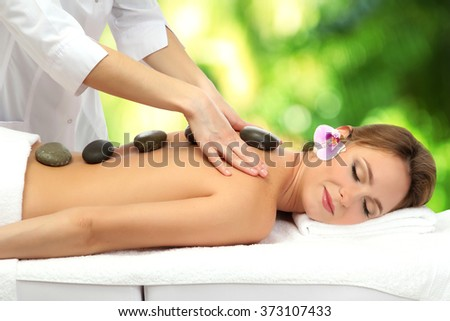 Beautiful woman with spa stones getting massage in spa salon