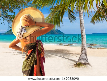 Beautiful woman with straw hat and sarong on the beach. Thailand. - stock photo