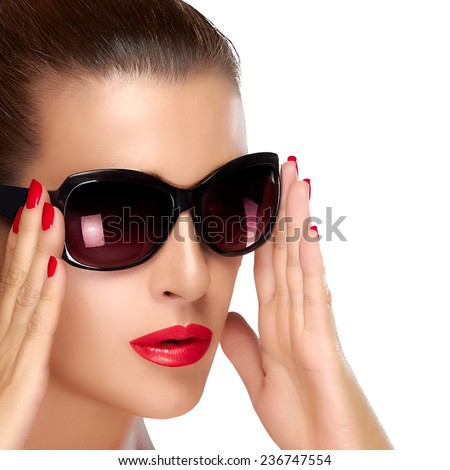 Beautiful woman with stylish oversized sunglasses. High fashion portrait isolated on white. Closeup face with raised hands to the sides of the glasses. Fashion, beauty and makeup concept