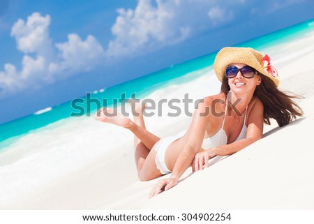 beautiful woman with sun hat and flower having fun at beach - stock photo