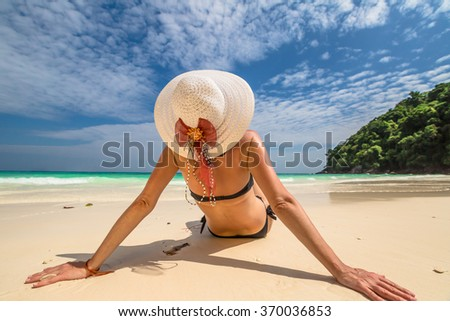 Beautiful woman with swimsuit and wide-brimmed hat relaxing on white sand tropical beach. Similan Islands National Park, Phang Nga, Thailand, one of the tourist attraction of the Andaman Sea.