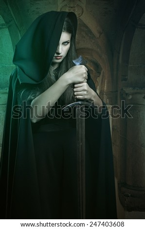 Beautiful woman with sword in a stone castle. Fantasy and legend  - stock photo