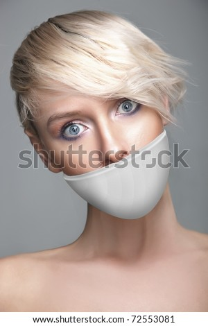 Beautiful woman with tape on mouth portrait