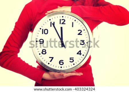 Beautiful woman with the clock. - stock photo