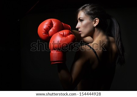 beautiful woman with the red boxing gloves,black background - stock photo