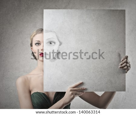 beautiful woman with transparent panel covering half her face - stock photo