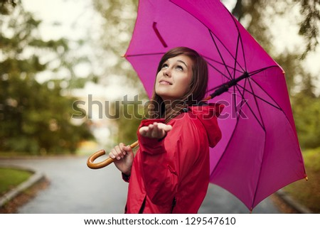 Beautiful woman with umbrella checking for rain - stock photo